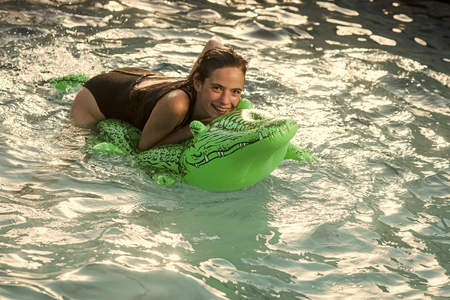 High fashion portrait of elegant woman. Beautiful woman in water with green Inflatable crocodile