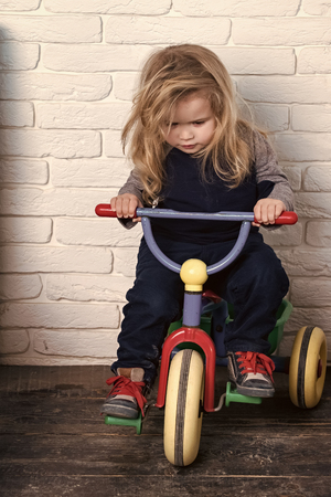 Child Childhood Children Happiness Concept. Boy riding bicycle in room