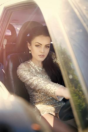 Fashion woman model posing. Woman driving car