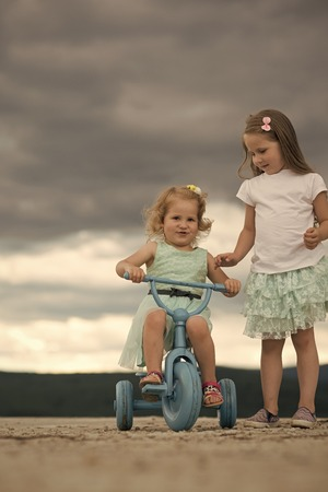 Child Childhood Children Happiness Concept. Girl ride tricycle with sister on cloudy sky