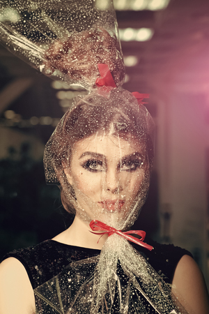 High fashion portrait of elegant woman. Girl with transparent wrapper on face, present
