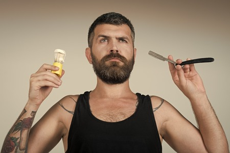 Man face handsome. Man cut beard and mustache with razor and shaving brush. 写真素材