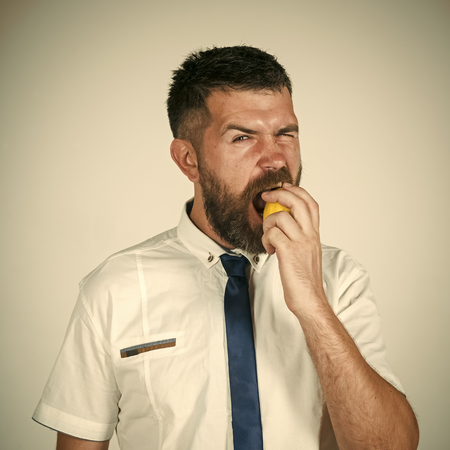Mens heals care. Man with long beard eat lemon. Фото со стока