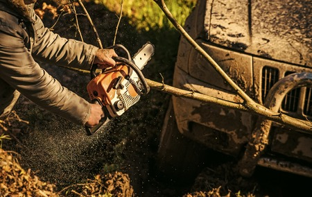 Ofroad for hard man. Male hands hold chainsaw and car covered with mud on sunny nature background. Sawing branch in front of bumper and light of SUV. Impassibility of roads concept. 写真素材