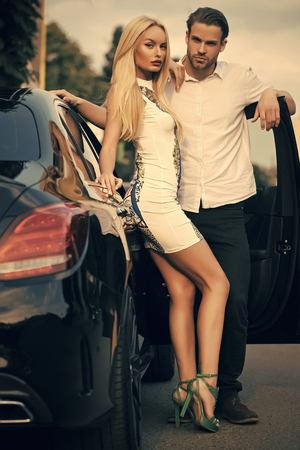 Female Face. Issues affecting girls. Sexy couple at car on summer day. Sensual woman and man at auto outdoor. Business trip, travel, business concept. Transport, transportation, vehicle. Luxury lifestyle, style. Date, love, romance Standard-Bild