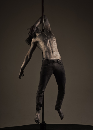 Fashion model Man fece close up. Face Man wiht happy emetion. Man with nude torso covered with shimmering silver paint, dark background. Athlete, sportsman performing pole dancing moves, work out, show trick. Guy hanging on metallis pole. Performance concept. Standard-Bild - 104608385