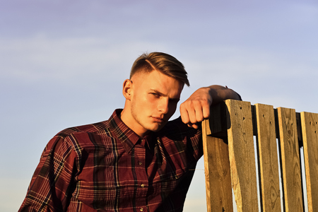 carpenter or woodworker in sunrise. carpenter young man at wooden fence on blue sky background.