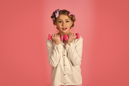 Face fashion little girl or kid in your web site. Little girl face portrait in your advertisnent. sport, morning exercise, weight lifting, pink background. Retro girl, fitness, diet. childhood, health, workout. child with dumbbells. Little girl with barbells, dieting, punchy pastels.