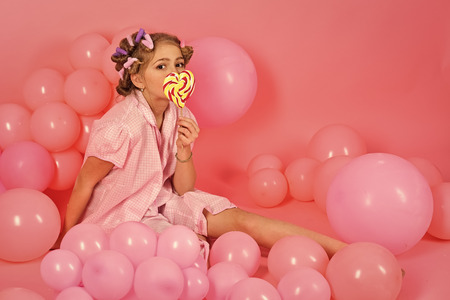 Kids face skin care. Portrait girl face in your advertisnent. Party balloons, kid in curlers, pajama fashion. party balloons on pink studio background, copy space Standard-Bild - 106019526