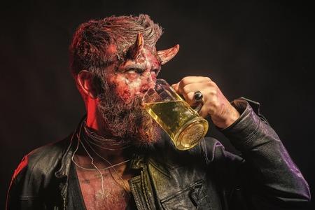Halloween man demon drinks beer on a black background. 写真素材