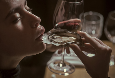 Female Face. Issues affecting girls. girl or woman eating oyster with wine in luxury restaurant. woman or girl eating oyster in hand and drink red wine