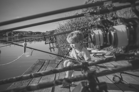 Child Childhood Children Happiness Concept. Summer vacation of little boy fishing on river. Stock Photo
