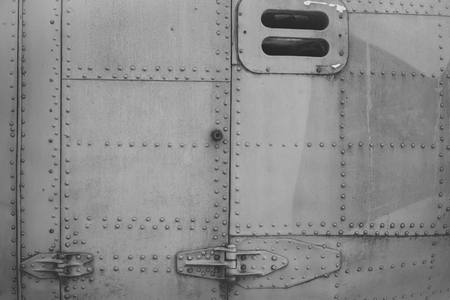 Old silver metal surface of the aircraft fuselage with rivets. Fuselage detail view. Airplane metallic fuselage detail with rivets. Imagens