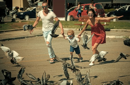 Child Childhood Children Happiness Concept. Happy family spend time together, urban background. Parents with son running near doves, chasing pigeons, happy boy with smiling face Stok Fotoğraf