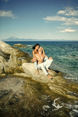 Passionate couple kissing, boy and girl.Sensual nude attractive couple on pensive faces. Sexy topless couple sits on stone or reef in sea.