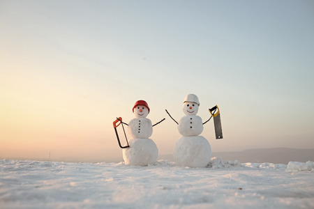 Happy New Year with Snowman. Snowmans happy couple. Snowmans celebration. Snowman builder in winter in helmet. New year snowman from snow with saw. Building and repair work.