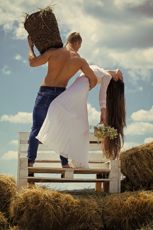 Couple in love. Fashion model woman fece close up. Face woman wiht happy emotion. Woman with long hair in white dress with flowers. Couple in love hug on bench on blue sky. Summer vacation concept. Man with muscular torso hold wicker basket. Romance, relationship, relations.