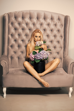 Women face skin care. Portrait women face in your advertisnent. Woman with flowers on grey sofa Stok Fotoğraf