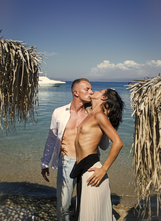 Romantic man and woman couple having intimate sex. Topless woman and man kissing near umbrella made out of dried palm leaves. Couple in love full of desire at beach, sea background. Couple on vacation at tropical seashore. Love concept.