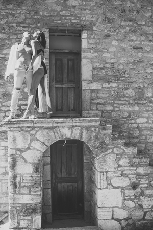 Prelude - couple in love. Woman in black lingerie, man with nude torso stands outdoor. Couple enjoys nudity. Sexy couple undressing under sunlight with ancient rocky wall and old door on background. P