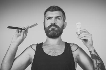 Man cut beard and mustache with razor and shaving brush.