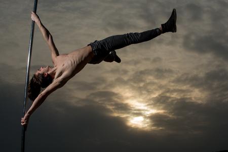 muscular man dance on pylon. muscular body of sportsman dancing on pole.