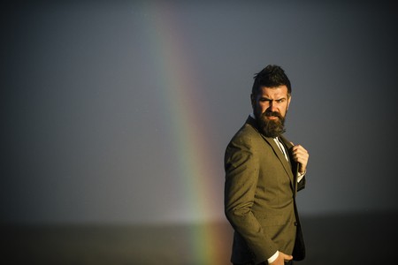 Hipster with beard and mustache on grey sky. Bearded man gay and rainbow. Fashion businessman in classic coat with bow tie. Vacation and wanderlust. Gender equality rights and freedom, copy space.