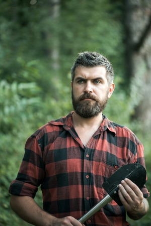 Brutal lumberjack wandering in wilderness. Ecologist exploring the woods. Young scientist with stylish beard working in nature. Environment and ecology concept. Фото со стока