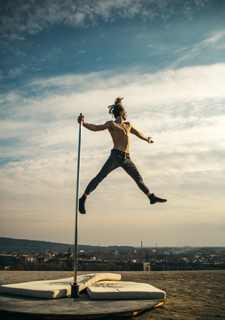 Sexy macho man fly on sky background. Pole dance sport. Strong man dancer workout on pole. Athletic guy make acrobatic elements on pylon. Young man dancing on pylon. Towards the healthier lifestyle