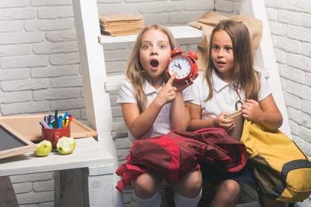 Late. Shoked small girls show time on clock. small kids late to school. Banque d'images - 104731685