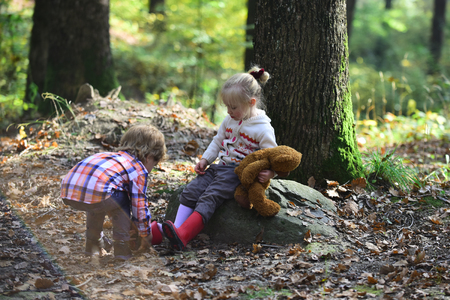 Little brother cares for baby sister in autumn city park. Stock Photo