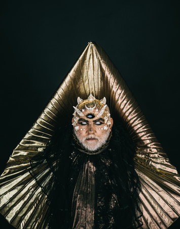 Wizard with blind eyes predicting future. Demon with golden collar isolated on black background, horror concept. Man with beard, fancy makeup portraying monster or mysterious beast, Halloween idea.