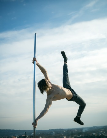 Pole dance sport. pole dance training of young man dancer on blue sky background