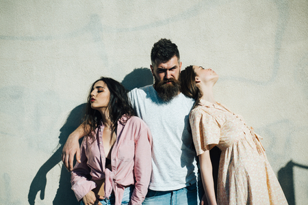 Bearded man standing between two beautiful women over white wall. Man making up his mind and choosing between impudent brunette and honest girl, love triangle, relationship problems concept.