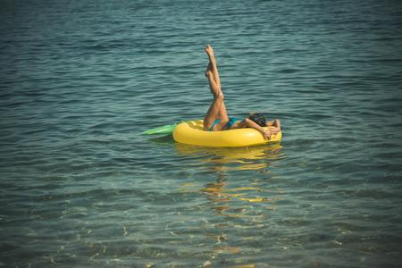 Enjoying suntan. Vacation concept. Top view of slim young woman in bikini holding yellow air mattress