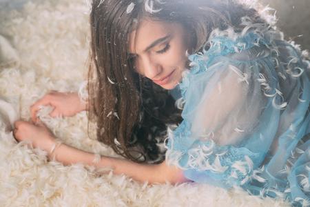 Mooi meisje met prachtig lang donker haar poseren op donzig bed. Mooie fee in blauwe jurk rustend op pluizige wolk. Schattige jonge dame liggend op witte veren, droomland concept.