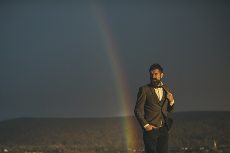 Fashion businessman in classic coat with bow tie. Bearded man gay and rainbow. Hipster with beard and mustache on grey sky. Vacation and wanderlust. Gender equality rights and freedom, copy space.