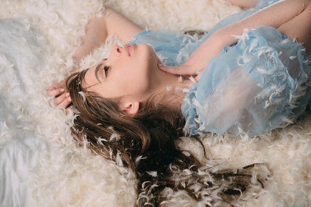 Dreamy girl fantasizing about future at bedtime. Teenager in blue silk nightgown lying in soft bed with white feathers. Joyful youth lifestyle and growing up concept.