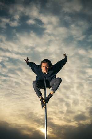 Pole dance fit man exercising with pylon outdoors in sunset