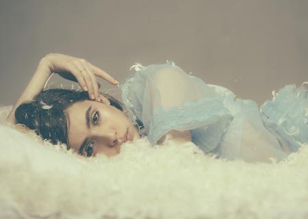 Hermosa chica en camisón de encaje azul posando en la cama mullida aislada sobre fondo gris. Hermosa mujer joven ahogándose en una nube suave llena de pequeñas plumas, partiendo hacia la tierra de los sueños, el concepto de hora de acostarse.