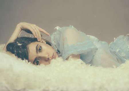 Lovely girl in blue lace nightgown posing on fluffy bed isolated on gray background. Beautiful young female drowning in soft cloud full of tiny feathers, departing for land of dreams, bedtime concept. 版權商用圖片