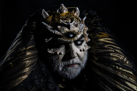 Man with dragon skin and gray beard, alien or reptilian makeup. Monster with sharp thorns and warts. Demon head isolated on black, horror and fantasy concept.