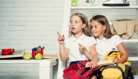 Children reading from books together while sitting down Stock Photo