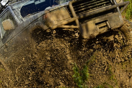 Car with strong chassis and the wheel axle crossing puddle with dirt splash. SUV takes part in racing and overcomes obstacles. Automobile racing, car wash and off road vehicle concept Stock Photo