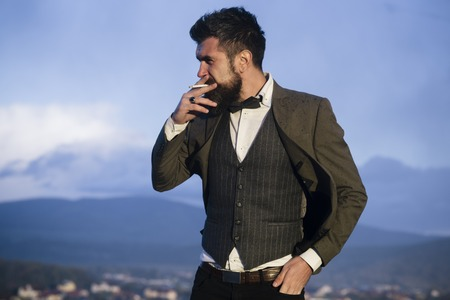 Fashion man smoking on mountain landscape. Fashion smoker with cigarette on fresh air.
