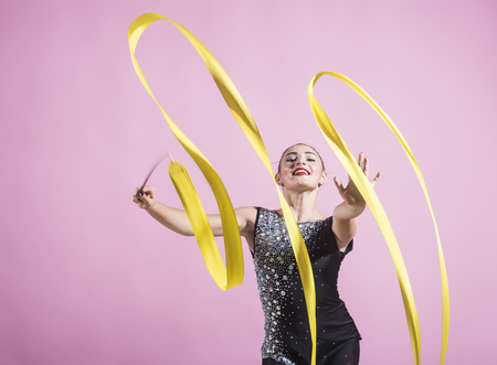 ribbon for rhythmic gymnastics at sport woman. ribbon for rhythmic gymnastics in hand of girl on pink background.