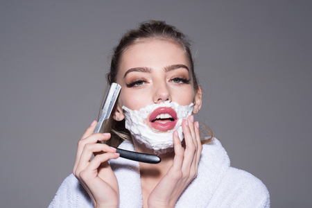 Girl on dreamy face wears bathrobe, grey background. Woman with face covered with foam holds straight razor in hand. Barber and shaving concept. Lady play with sharp blade of straight razor.