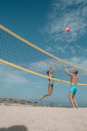 Summer vacation and travel on holiday in Miami. Sexy woman and muscular man with ball at net. Love and flirting of couple. Couple in love play volleyball on sunny beach. Sport activity and health.