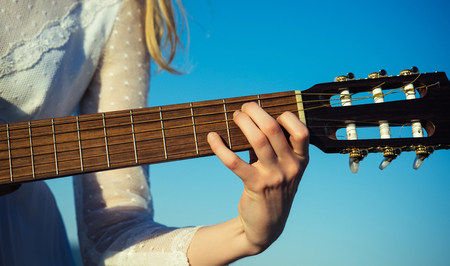 Female hand playing guitar. Guitar play, closeup of guitarist hand playing guitar. 版權商用圖片