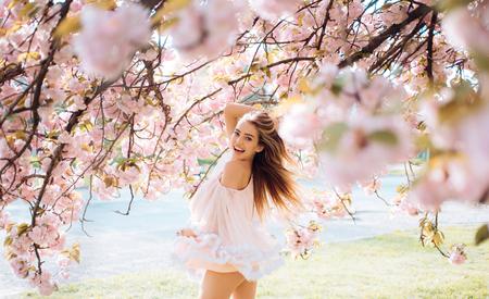Frau mit herrlichem Lächeln, das Spaß im blühenden Garten hat. Frau mit schlankem Körper auf natürlichem Hintergrund, Wellness- und Fitnesskonzept. Sinnliches blondes Mädchen im kurzen Chiffonkleid, das im Park geht.
